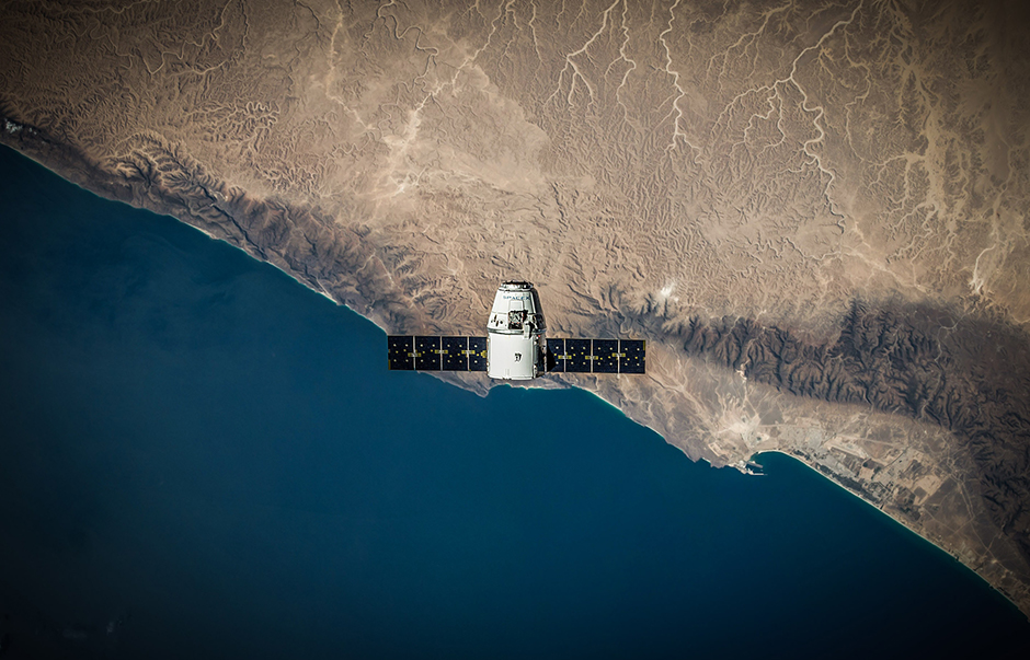 A satellite in orbit above a coastline
